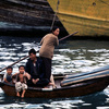 Activities in Hong-Kong bay, boat with man, woman and children