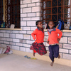 Young girls skipping in schoolyard