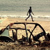 A man walking on a polluted beach.