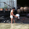 Man washing earthenware jar in river;