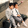 Two young boys sitting on a stone bench
