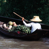 man on the water transporting fruit and vegetables