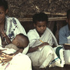 Literacy class, adult education, woman and three children