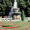 One of the fountains the park of the castle, trees, flower-beds, visitors