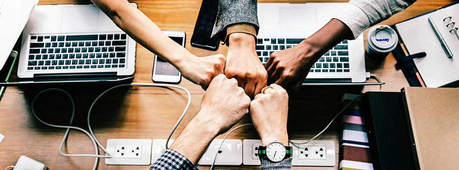 Fists with a variety of skin tones meed together above laptop computers on a wooden table
