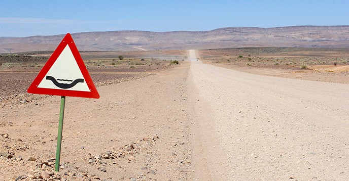 Flood warning sign along a gravel road, Namibia